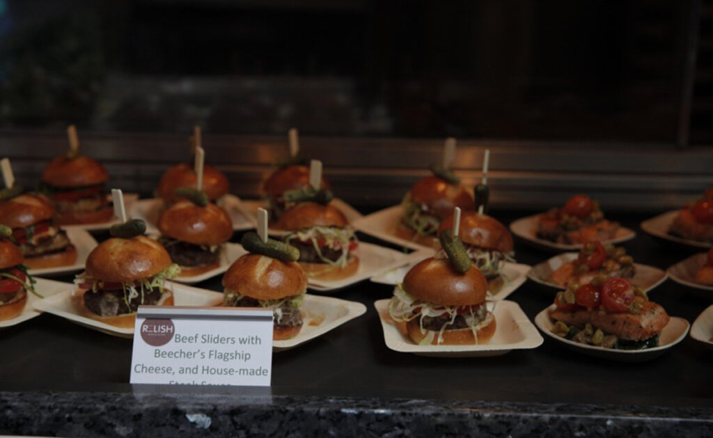 table with plates of beef sliders at an event