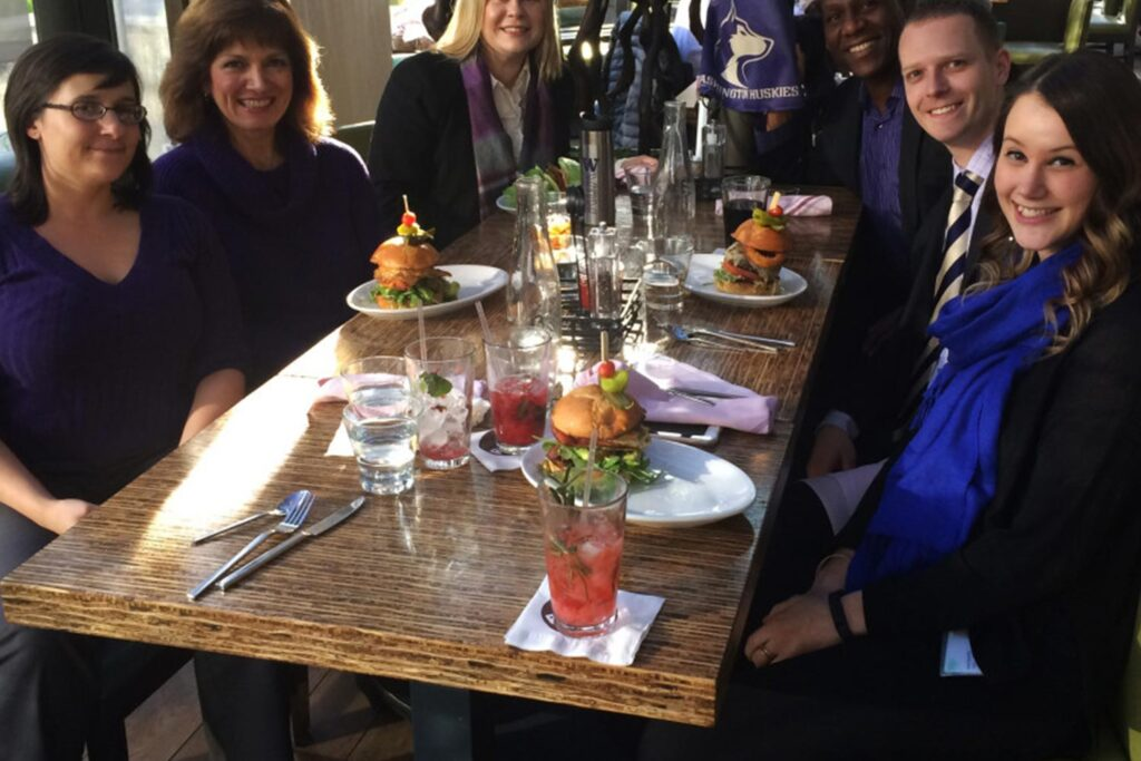group of people smiling for a photo at a wooden table with burgers and cocktails