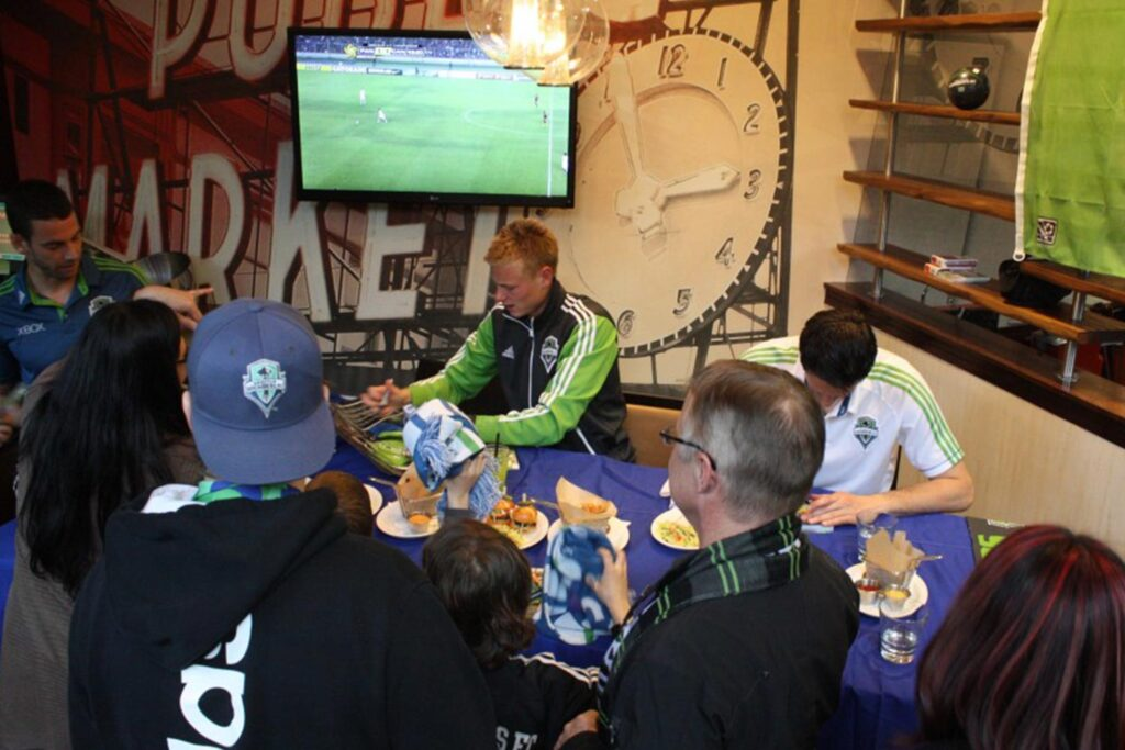 two soccer players on Sounders FC signing autographs at Relish Burger Bistro
