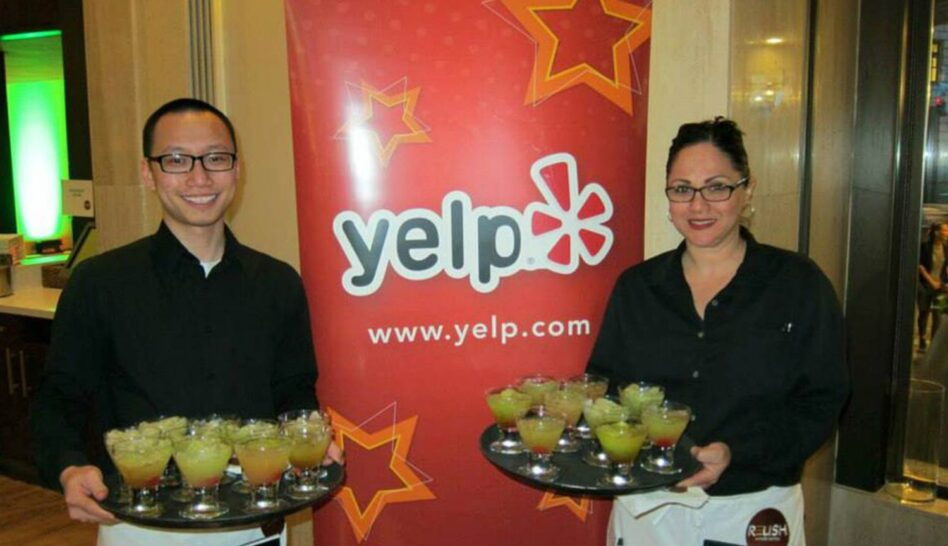 two waiters standing in front of a Yelp sign with trays of cocktails