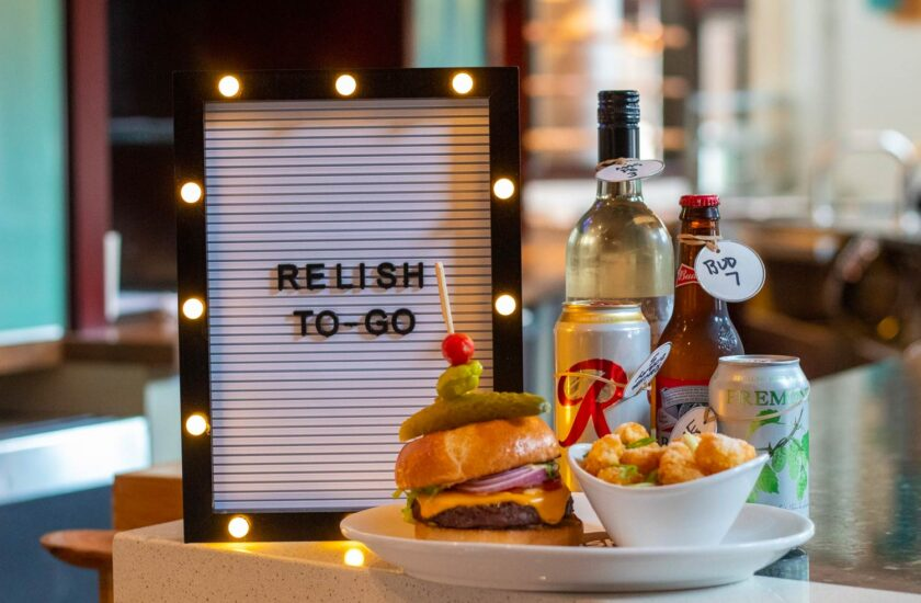 relish to go board next to a burger and bottles of beer