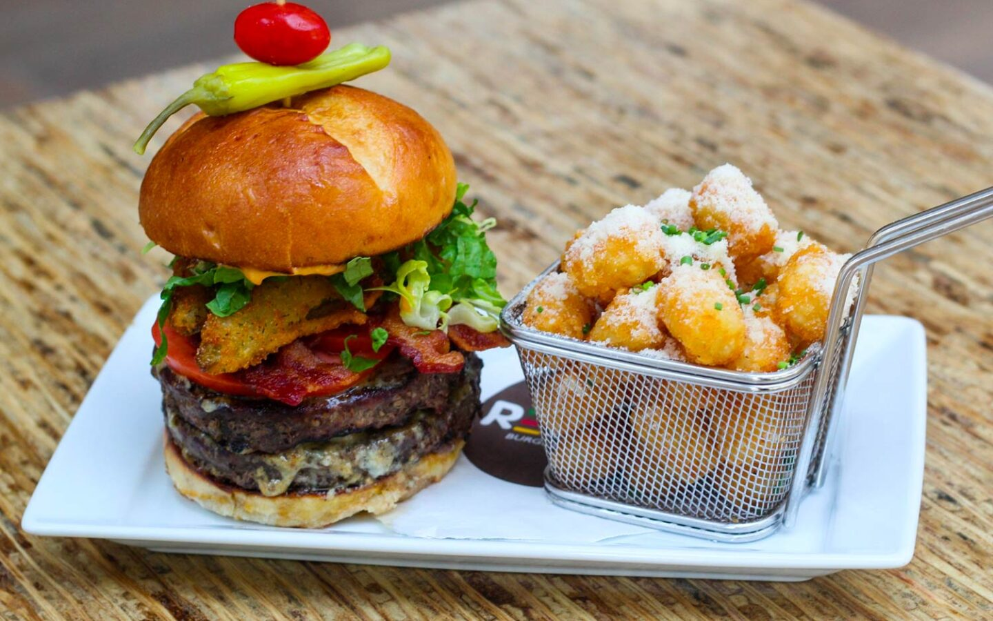 plate with a burger next to a basket of home fries