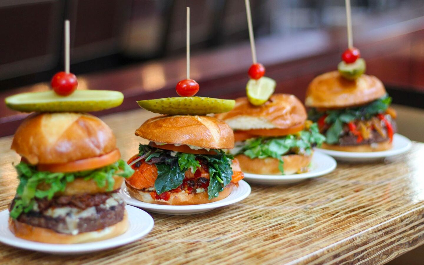 four different burgers in a line on a wooden table