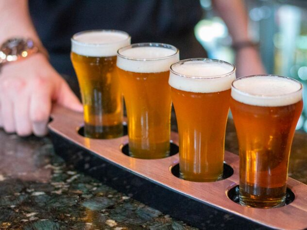 person holding a tray of four full pints of beer