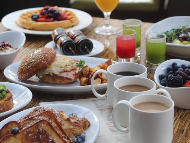 wooden table with different breakfast dishes, juices, and coffees