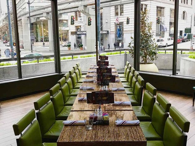 long rectangular dining table with green leather chairs next to a wall of windows