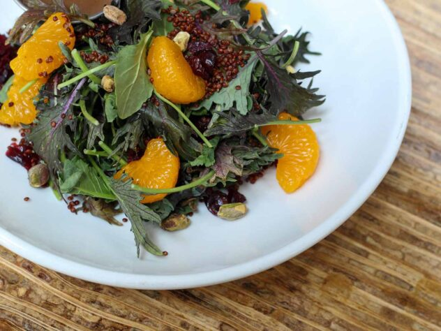 closeup of a salad with leafy greens and slices of orange