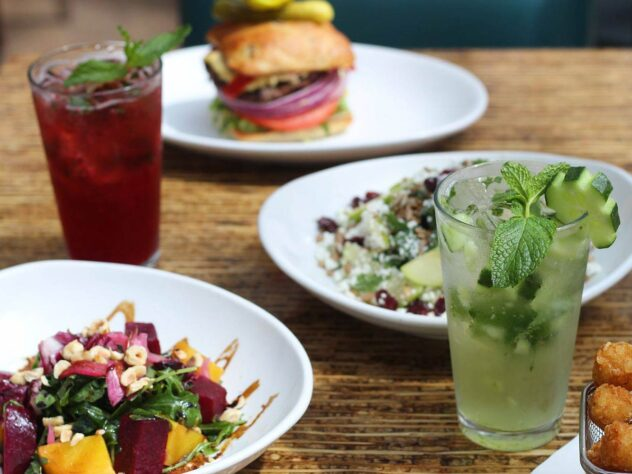 wooden table with salads on it next to a burger and two cocktails