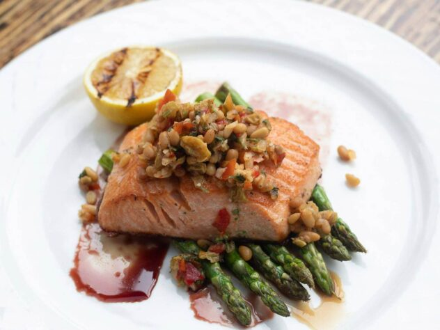 cooked salmon on asparagus next to a slice of lemon on a white plate