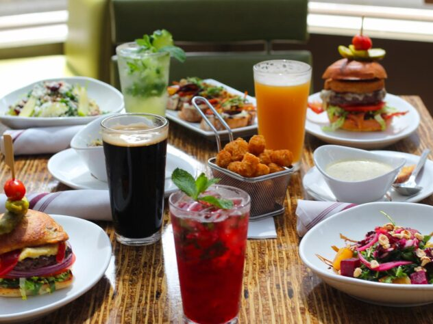 wooden table with different burgers, salads, and drinks on it